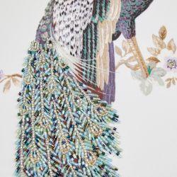 cojín bordado con pavo real y decorado con cuentas de cristal