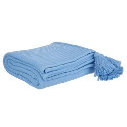 colcha azul acanalada con borlas en las esquinas de diseño