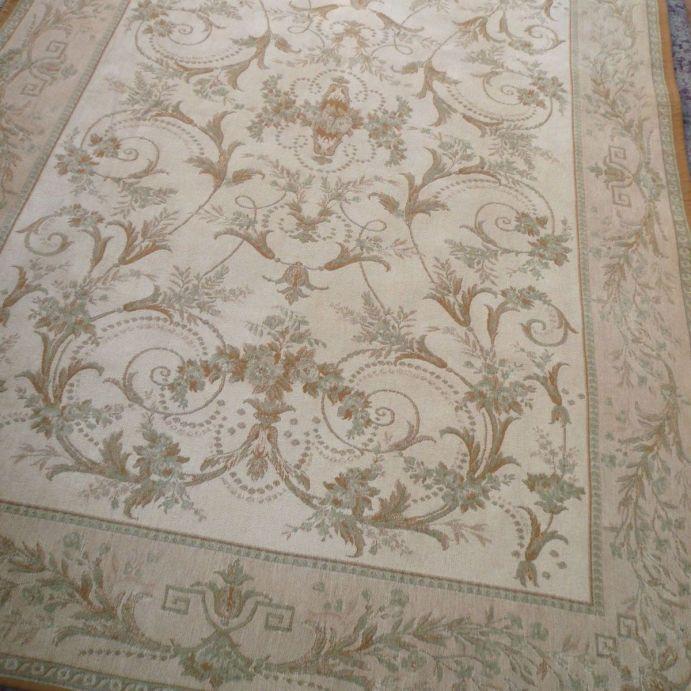 alfombra de lana de diseño clásico con cenefa y flores en tonos verde agua y natural