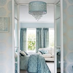 papel pintado con estampado de grandes topos de flores en color azul verdoso con brillo