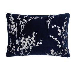 cojín azul oscuro bordado con ramas blancas de diseño