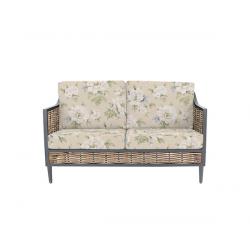 sofa para jardín de ratán roble con detalles en negro y cojines con estampados de diseño